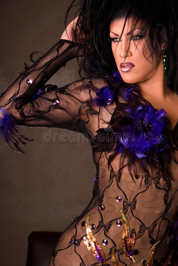 Drag queen wearing lace outfit. Drag queen wearing a black and purple lace and feather outfit, she is looking to the side. Professional hair and make-up stock photos
