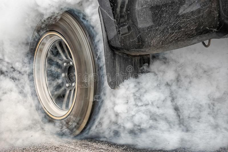 Drag racing car burns tire for the race. Drag racing car burns rubber off its tires in preparation for the race stock photography