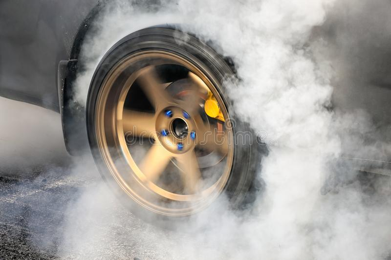 Drag racing car burns tires for the race. Drag racing car burns rubber off its tires in preparation for the race royalty free stock photos