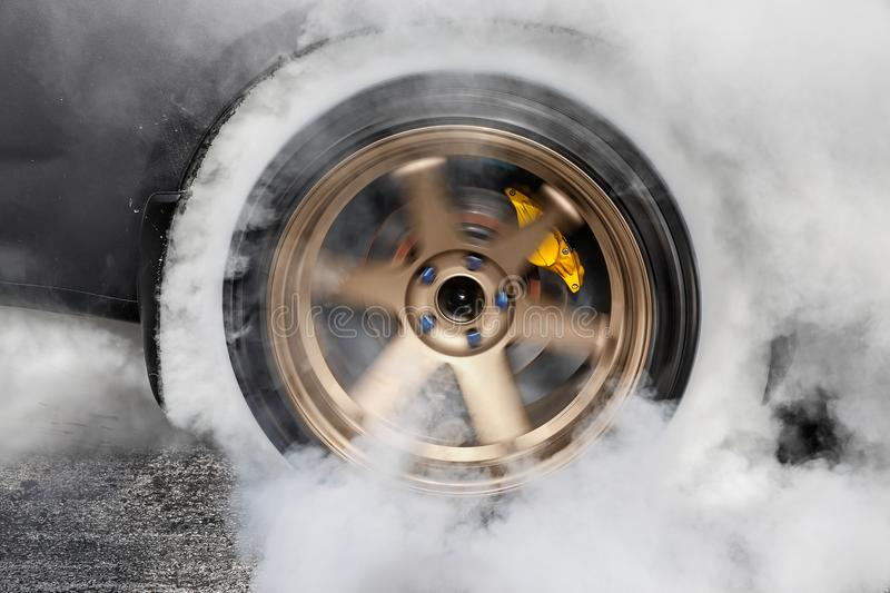 Drag racing car burns tire in preparation for the race. Drag racing car burns rubber off its tires in preparation for the race stock photo