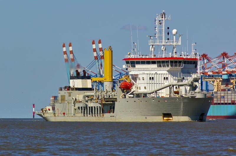 Draga de la tolva de la succión que se arrastra en el estuario de Weser con el portacontenedores e instalaciones de puerto en el  fotografía de archivo