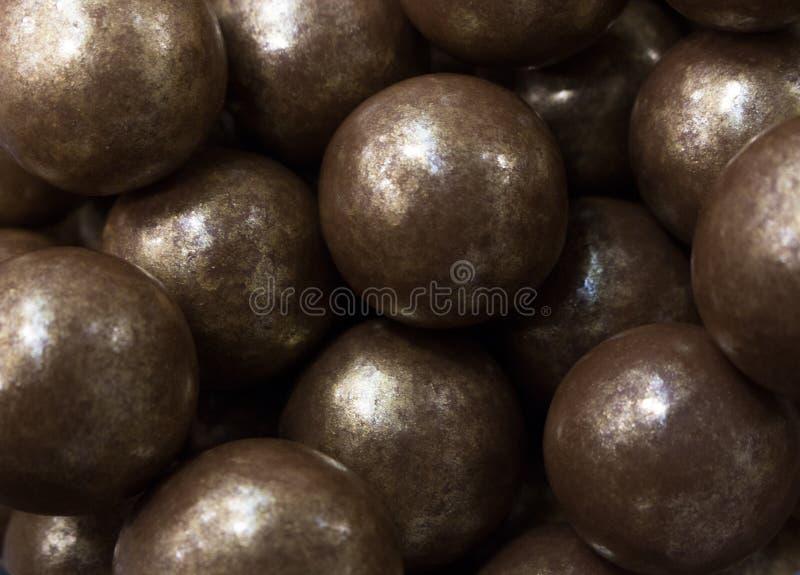 Dragee στη σοκολάτα γάλακτος με τα χρυσά βότσαλα στοκ εικόνα με δικαίωμα ελεύθερης χρήσης