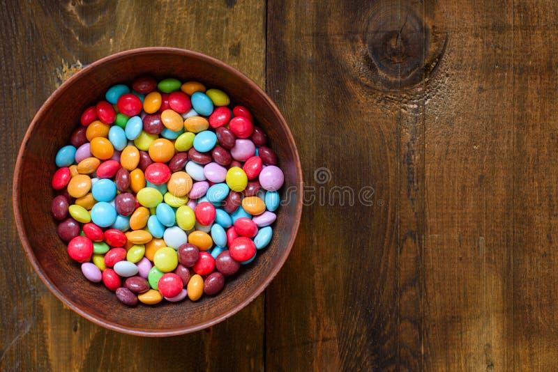 Dragee конфеты десерта пасхи красочный в шаре на темном деревянном столе скопируйте космос стоковые фото
