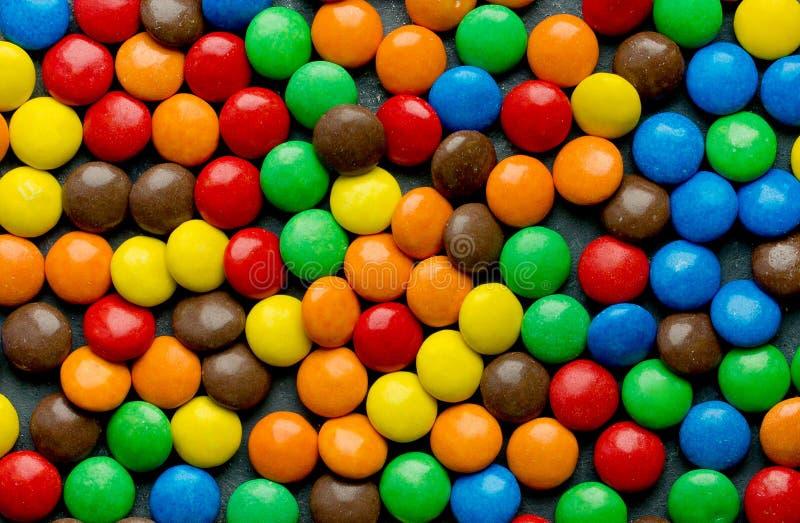 Dragees καραμελών σοκολάτας κάλυψαν το ζωηρόχρωμο λούστρο ως υπόβαθρο στοκ φωτογραφίες