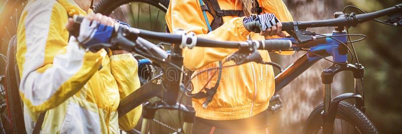 Dragende de bergfiets van het fietserpaar stock foto