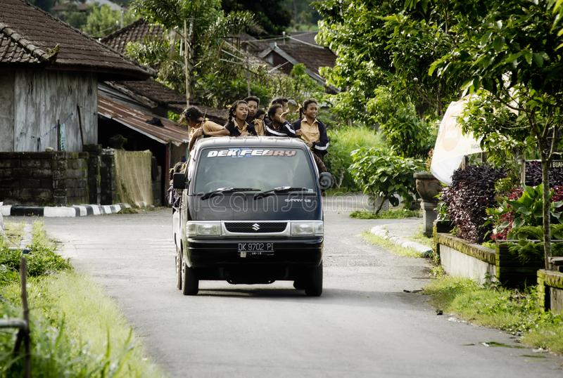 Dragende de schoolmeisjes van de schoolbus terug naar hun huis stock afbeelding
