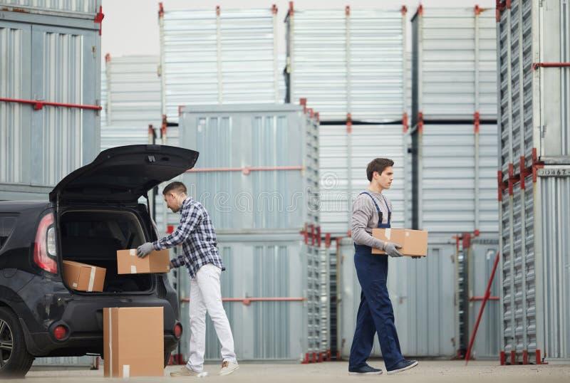 Dragende dozen van auto aan container stock fotografie