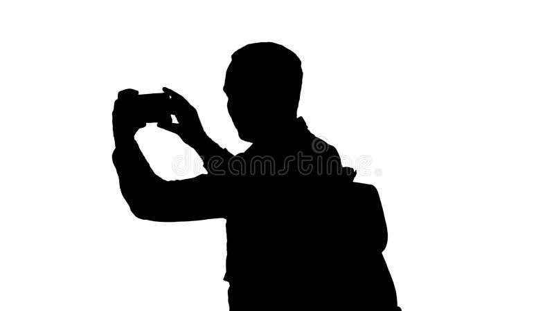 Dragende rugzak van de silhouet de knappe jonge mens en het nemen van een beeld van zich royalty-vrije illustratie
