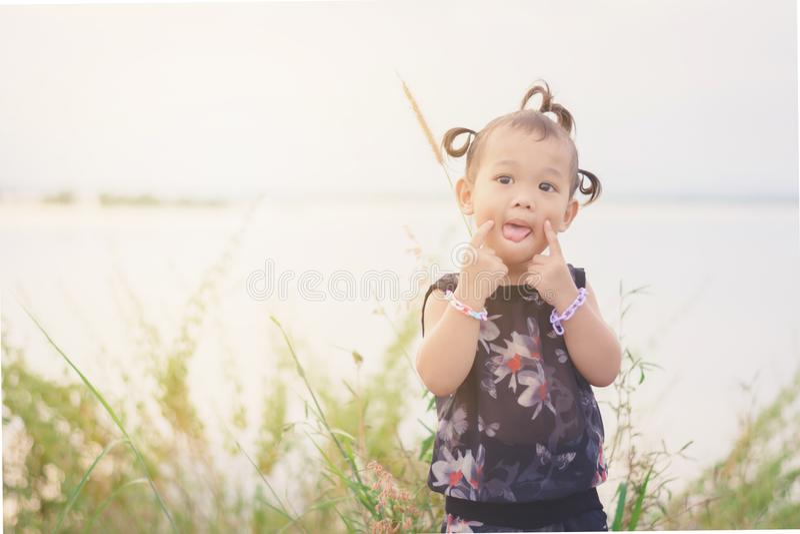 Draget av sötsaken och den gulliga asiatiska ungen med hår flätar ut dörren royaltyfria bilder