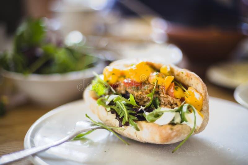 Draget fegt i hemlagat bröd med arugulasallad, mango, toma fotografering för bildbyråer