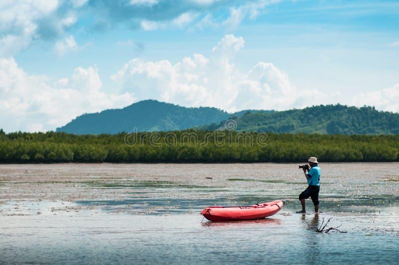 draging在桐树泥泞的土地的地方泰国人橙色颜色皮船  免版税库存照片