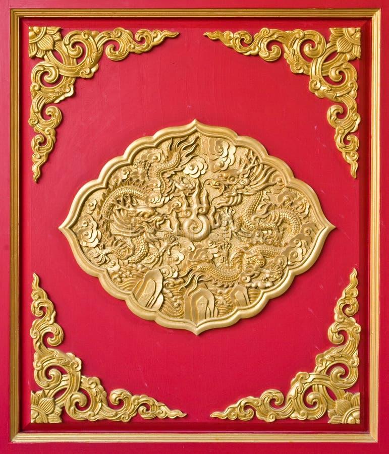 Drago dorato decorato su legno rosso fotografie stock