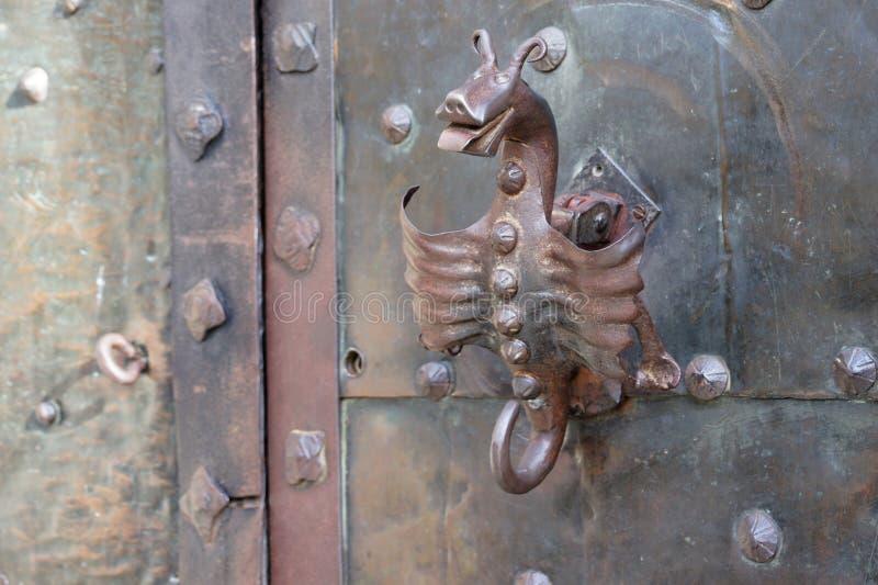 Drago metallico come maniglia della porta sul castello di Orava fotografia stock