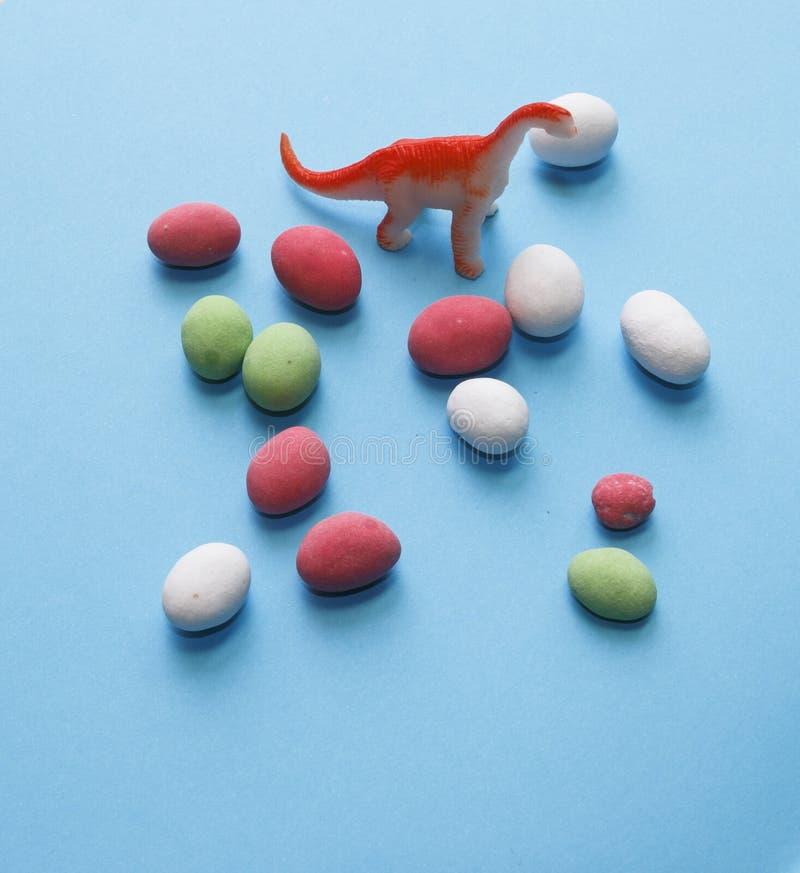 Drago, pastelli colorati, arachidi a colori glassa su un tabl blu fotografia stock