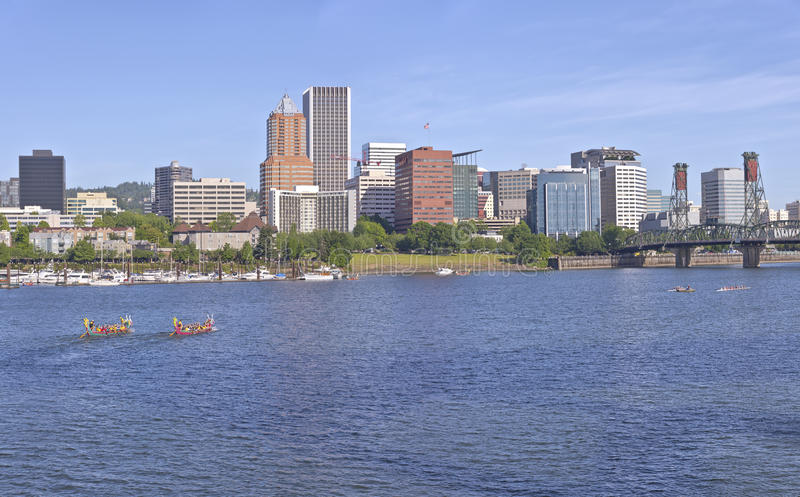 Dragon boats annual races and Portland Oregon skyline. Portland Oregon skyline and dragon boats rowing in morning light royalty free stock photos