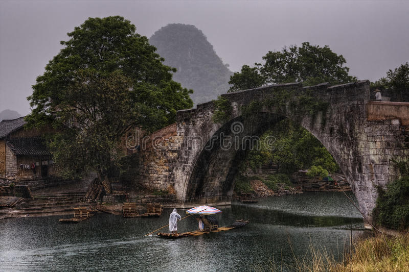 Dragon Bridge in Yulong Village, Yangshuo, Guilin, Guangxi Province, China. Yangshuo, Guangxi, China - March 31, 2010: Dragon Bridge in Yulong Village, tourists royalty free stock photography