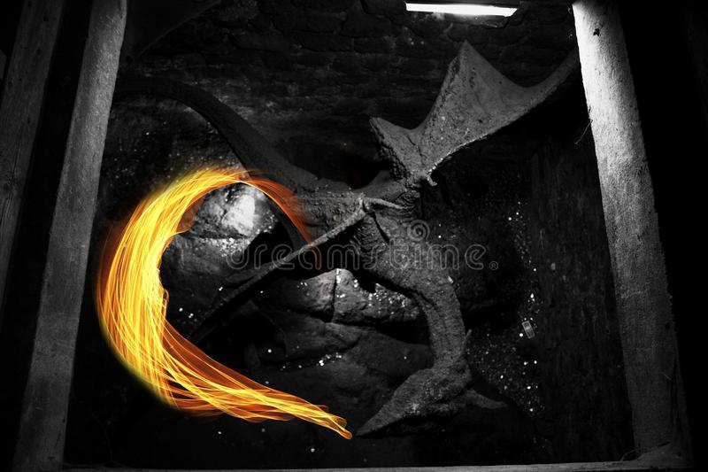 A black dragon spits fire in the basement of an old castle. stock image