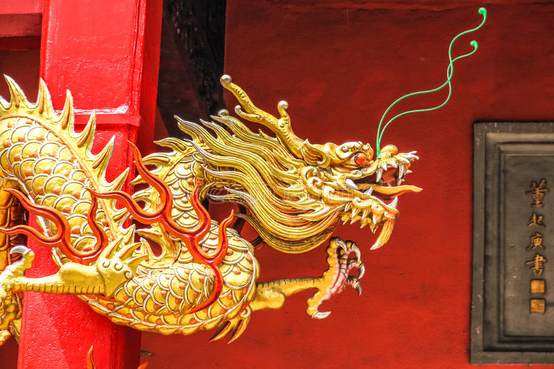 Dragon chinois d'or sur le mur rouge photographie stock