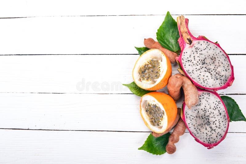Dragon Fruit, Passiebloem, Tamarinde en Papaja Verse tropische vruchten Op een houten achtergrond stock afbeelding