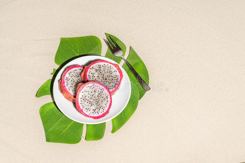 Dragon fruit, pitaya on palm tree leaves on the sand of tropical beach. Exotic food, snack. Summer travel. stock photography