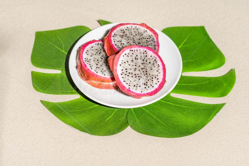 Dragon fruit, pitaya on palm tree leaves on the sand of tropical beach. Exotic food, snack. Summer travel. royalty free stock image