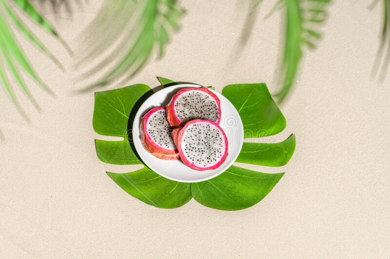Dragon fruit, pitaya on palm tree leaves on the sand of tropical beach. Exotic food, snack. Summer travel. royalty free stock photography
