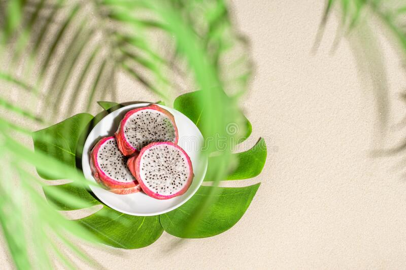 Dragon fruit, pitaya on palm tree leaves on the sand of tropical beach. Exotic food, snack. Summer travel. stock images