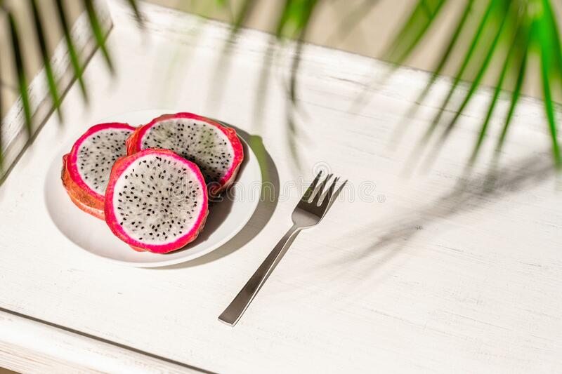 Dragon fruit, pitaya on a white wooden tray on the sand of tropical beach under a palm tree. Exotic food, snack. Summer travel. stock image