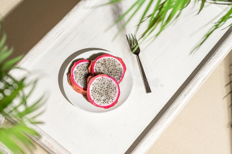 Dragon fruit, pitaya on a white wooden tray on the sand of tropical beach under a palm tree. Exotic food, snack. Summer travel. royalty free stock photo