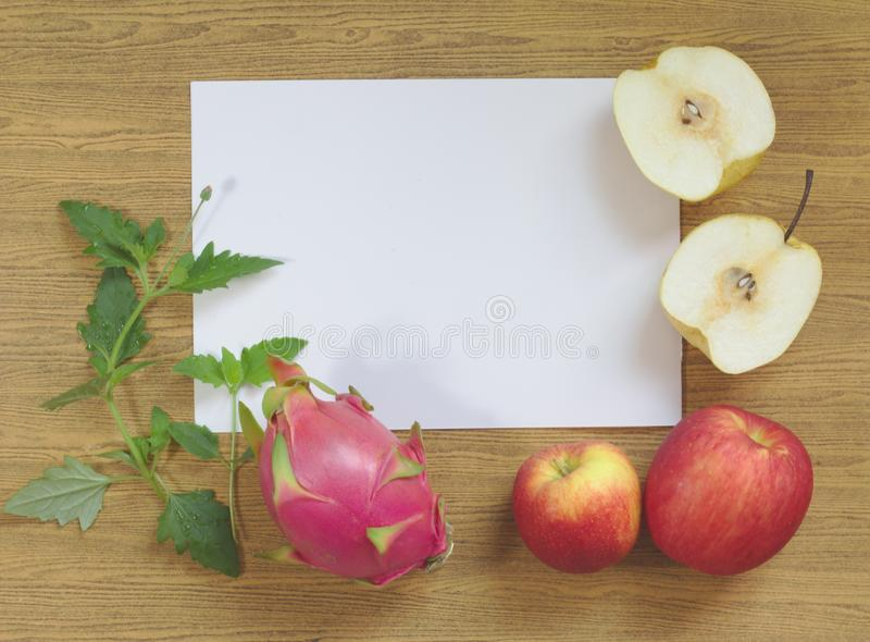 Dragon fruit, purple, yellow wheelbarrow Yellow-red apples on white paper, leaves, wood background, royalty free stock image