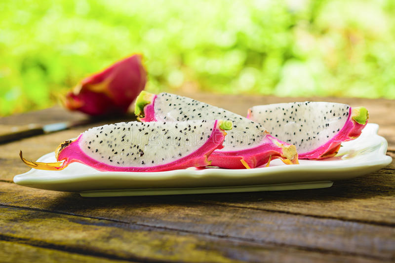 Dragon fruit slice in white dish on old wooden table and nature background. stock photos
