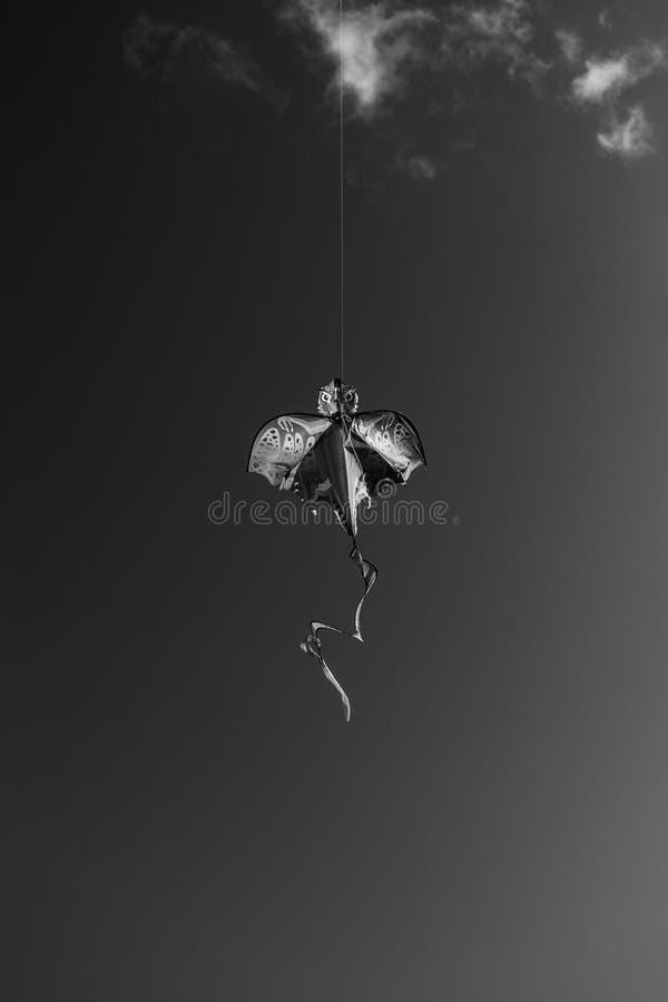 Dragon kite. Black and white image of a dragon kite soaring through an almost empty sky royalty free stock photo