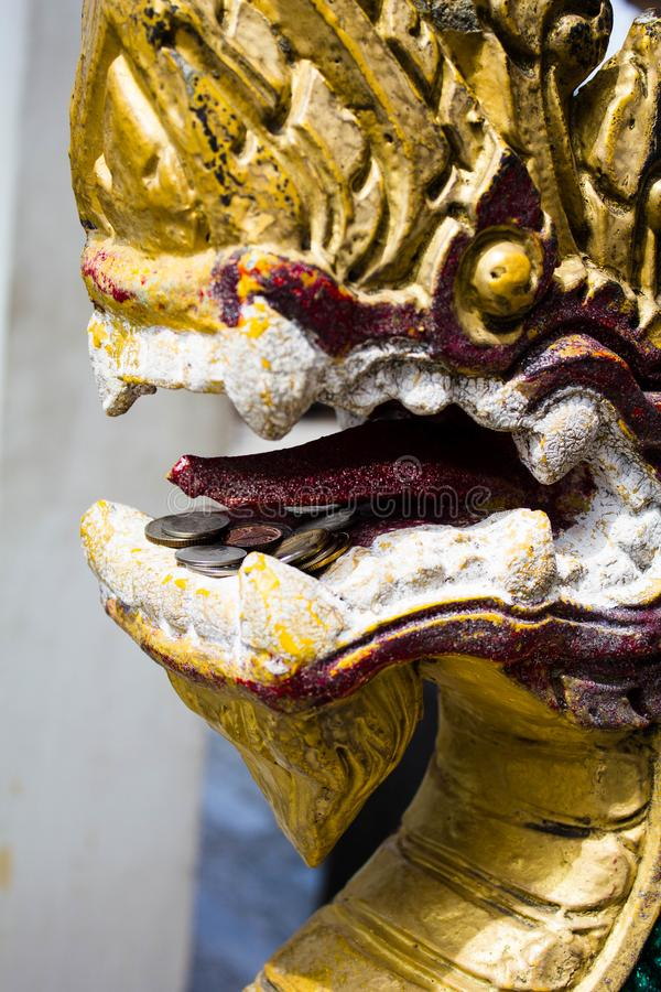 Dragon Laos Buddhist ancient sculpture. Golden dragon head closeup in Thailand in the temple stock photos