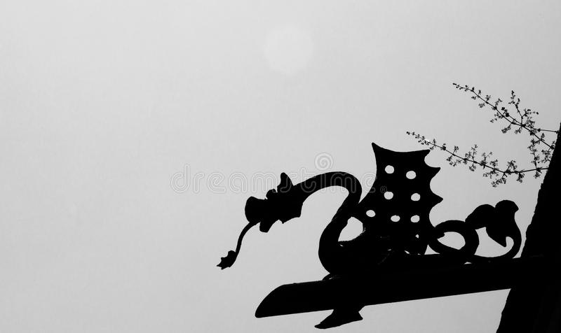 Dragon silhouette on the sky. Shot in black and white detail of the sculpture on the facade of this historic building cemetery representing some characters / stock photography