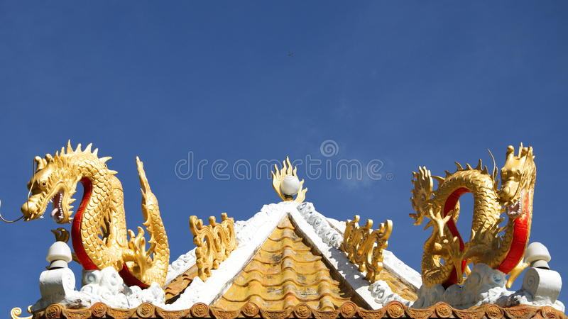 Dragons on Chinese shrine. Rooftop soaring into blue sky stock images