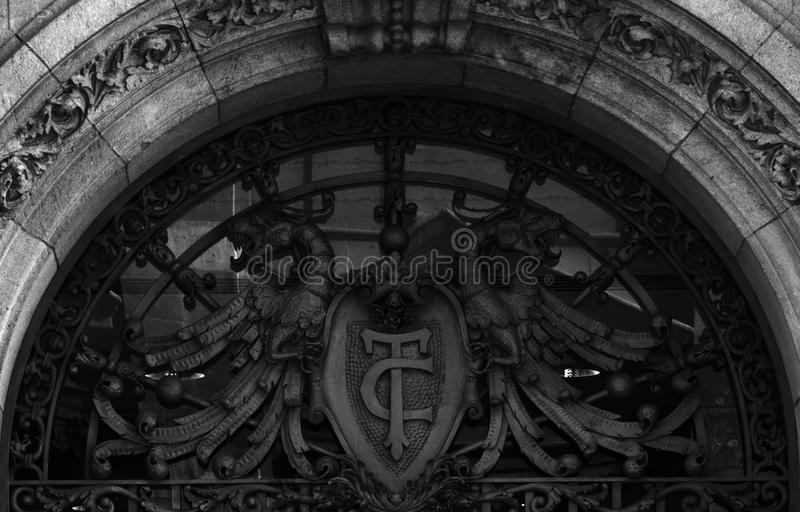 Dragons on the door. Shot in black and white, detail on an iron sculpture representing two dragons placed on the door of this historic building, set in Eixample stock images