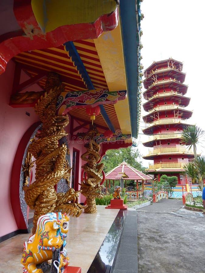 Dragons et lions d'or jumeaux dans le temple avec la tour rouge et jaune de fond de la pagoda Ekayana photo libre de droits
