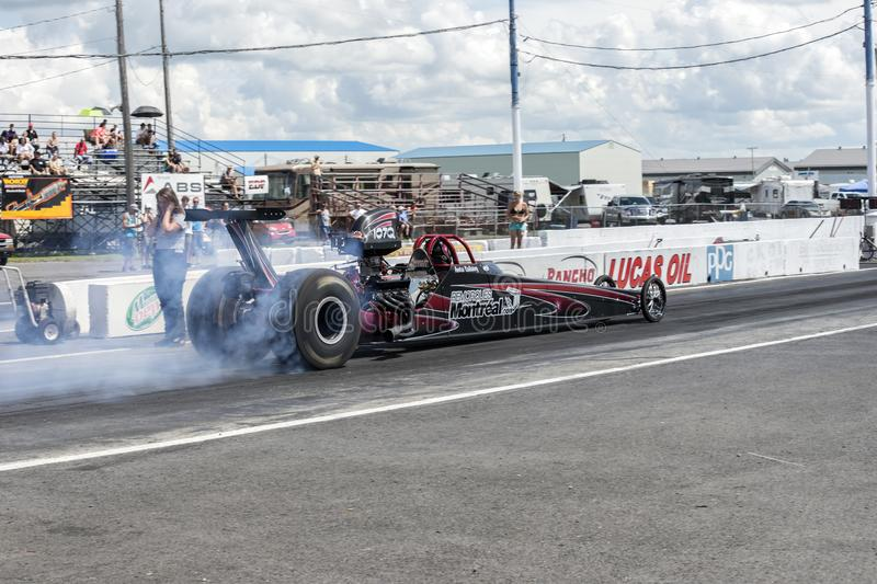 Dragster smoke show. Rear side view of dragster on the track at the starting line making a smoke show during the john scotti all out august 17, 2017 royalty free stock photo