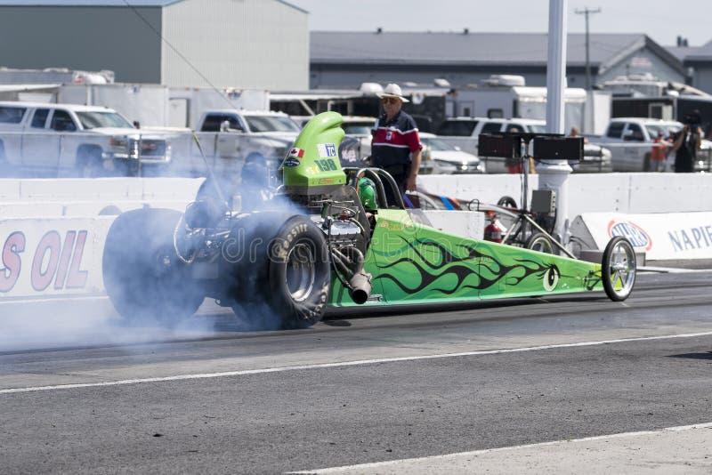 Dragster superiore del combustibile che fa una manifestazione del fumo sulla pista di corsa alla linea di partenza fotografia stock libera da diritti