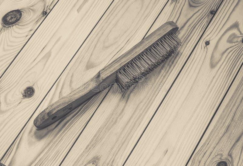 Drahtbürste mit Holzgriff auf rohem hölzernem Hintergrund lizenzfreies stockfoto
