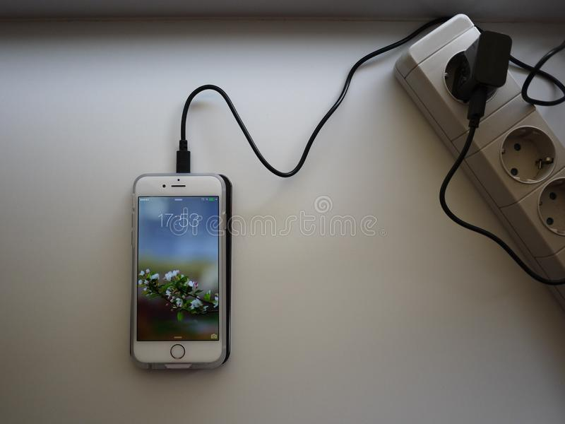 Drahtlose Aufladung f?r Smartphone Der Smartphone wird aufgeladen, wenn es auf die Oberfl?che der Station gesetzt wird sonderkomm stockfotos