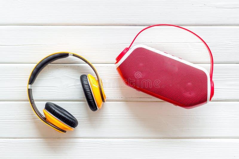 Drahtlose Kopfhörer und tragbarer Sprecher auf weißem hölzernem copyspace Draufsicht des Hintergrundes stockfotos