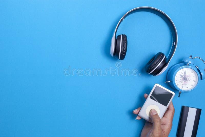 Drahtloser Kopfh?rer und Multimedia-Spieler, blauer Wecker auf Hintergrund des blauen Papiers, Bild f?r Medien entwerfen und Musi stockbild