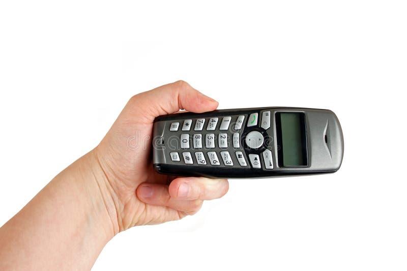 Drahtloses Telefon in der Hand mit der Hand festgemacht lizenzfreie stockfotografie