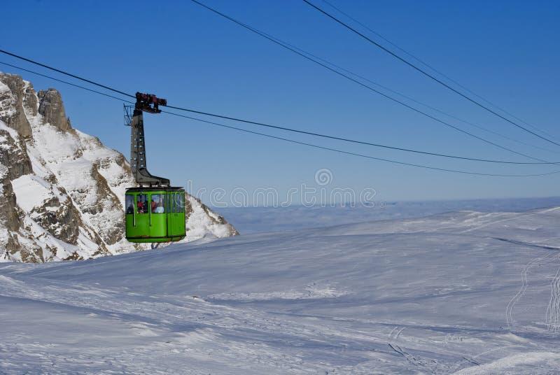 Drahtseilbahn über schneebedecktem Berg stockfotografie