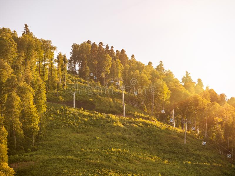 Drahtseilbahn auf einer grünen Steigung belichtet durch die Sonne bei Sonnenuntergang stockbild