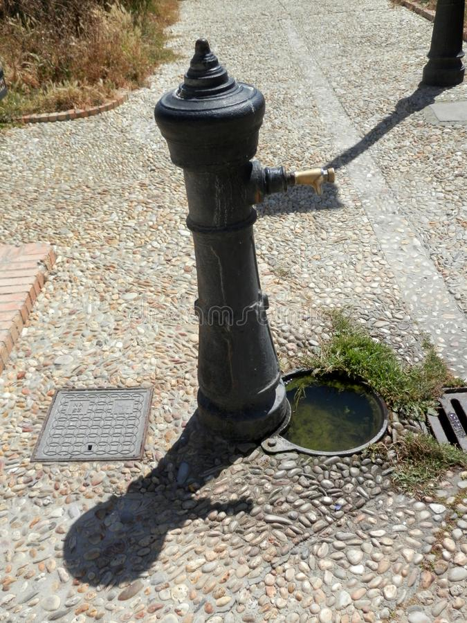 Drain and cast iron pump in Tarifa square royalty free stock images