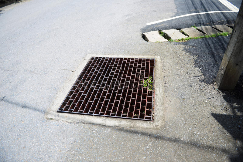Drain. Melted water flows down through the manhole cover stock photos