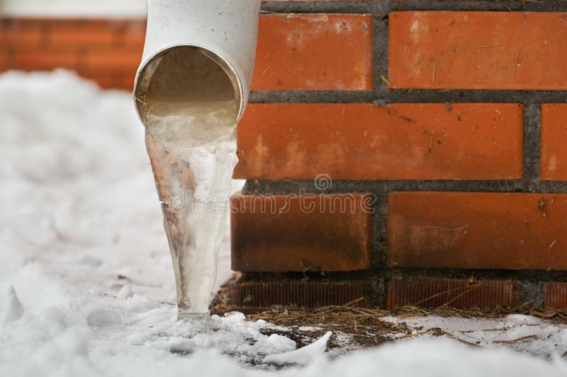 Drain pipe with frozen stream of water near house brick wall. Drain pipe with frozen stream of water near brick wall of a cottage outdoors in winter stock photo