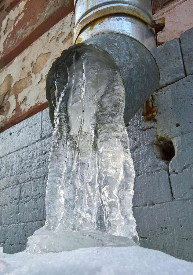 Drain pipe with frozen water. On the wall stock photos